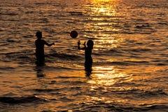 Kinderen die bij Zonsondergang spelen Royalty-vrije Stock Foto's
