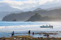 Kinderen die bij zonsopgang op een strand van Palawan naast de beroemde Ondergrondse Rivier spelen Stock Fotografie