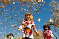 Kinderen die in bladeren spelen stock afbeelding