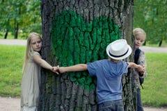 Kinderen die boom omhelzen milieubescherming openluchtaard Behoud in openlucht stock foto