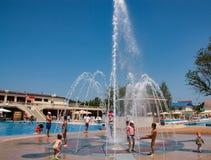 Kinderen die in de fontein in het park spelen Stock Fotografie