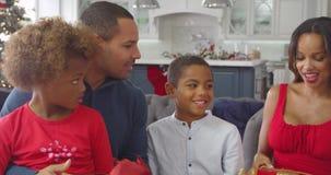 Kinderen die de giften van ouderskerstmis thuis geven - zij schudden pakketten en proberen om te veronderstellen wat binnen is stock videobeelden