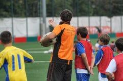 Kinderen die in de school van het voetbalvoetbal met instructeur spelen stock afbeelding