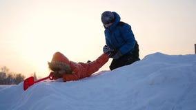 Kinderen die in de winter op een sneeuwberg tegen de hemel spelen stock video