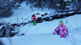 Kinderen die in de wintersneeuw door rivier spelen Stock Afbeelding