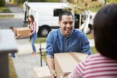 Kinderen die Dozen van Van On Family Moving In-Dag helpen leegmaken stock foto's