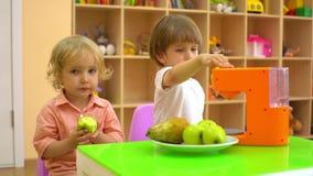 Kinderen die een appel in peuterlunch in peuterklas eten stock video