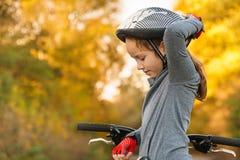 Kinderen die een fiets op een oprijlaan leren buiten te drijven Meisjes die fietsen berijden op asfaltweg in de stad die helmen d stock fotografie