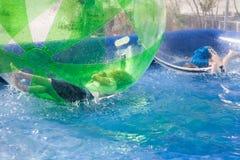 Kinderen die in een opblaasbare plastic ballon op het water spelen Royalty-vrije Stock Afbeelding