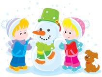 Kinderen die een Sneeuwman maken Stock Foto