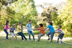 Kinderen die een touwtrekwedstrijd in park hebben Stock Foto