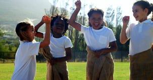 Kinderen die een zakrace in park spelen stock footage