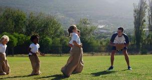 Kinderen die een zakrace in park spelen stock video