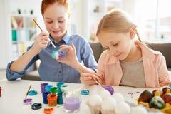 Kinderen die Eieren schilderen voor Pasen stock afbeelding