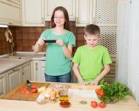Kinderen die eigengemaakte pizza thuis keuken koken Glimlachend meisje Ta Royalty-vrije Stock Foto