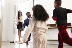 Kinderen die en Werkende Ouders begroeten koesteren aangezien zij Huis van het Werk terugkeren stock foto's