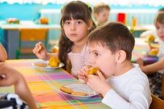 Kinderen die gebakken appel en koekje eten bij opvang royalty-vrije stock foto