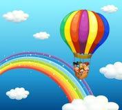 Kinderen die in grote ballon over de regenboog berijden Stock Foto