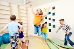 Kinderen die gymnastiek van klasse genieten Stock Afbeeldingen