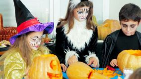Kinderen die in Halloween-Kostuums Pompoenen snijden stock video
