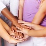 Kinderen die handen stapelen als symbool voor groepswerk Royalty-vrije Stock Foto's