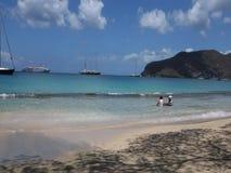 Kinderen die in het Caraïbische overzees met passagiersboten spelen op de achtergrond stock video