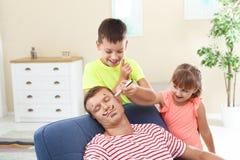 Kinderen die het gezicht van hun vader schilderen terwijl hij slaap royalty-vrije stock afbeelding