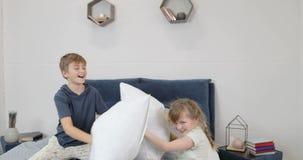 Kinderen die het hebben van pret in oudersbed het vechten hoofdkussens, gelukkige familie in slaapkamer in ochtend hebben stock footage