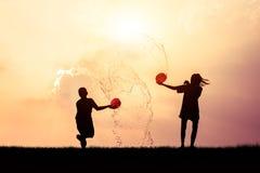 Kinderen die het silhouet van Songkran van het plonswater spelen Royalty-vrije Stock Afbeelding