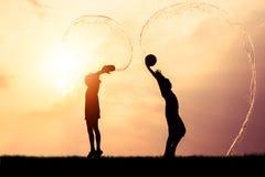 Kinderen die het silhouet van Songkran van het plonswater spelen Stock Foto's