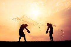 Kinderen die het silhouet van Songkran van het plonswater spelen Royalty-vrije Stock Foto's