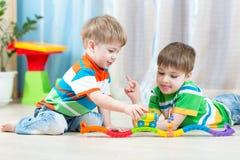 Kinderen die het stuk speelgoed van de spoorweg in kinderdagverblijf spelen royalty-vrije stock fotografie