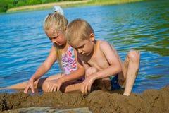Kinderen die in het zand spelen Stock Foto's