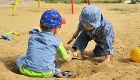 Kinderen die in het zand spelen Stock Afbeelding