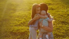 Kinderen die hun moeder koesteren bij zonsondergang stock video