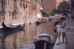 Kinderen die in kanaal in Venetië vissen Stock Afbeelding