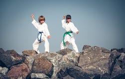 Kinderen die karate op de steenkust opleiden stock fotografie