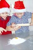 Kinderen die Kerstmiscake voorbereiden Stock Foto's