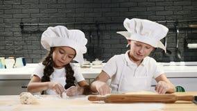 Kinderen die in keuken koken Twee kleine jonge geitjes in het broodjesdeeg die van chef-kokhoeden hebbend pret glimlachen 4K stock footage
