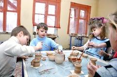 Kinderen die klei in aardewerkstudio vormen Stock Foto