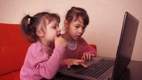 Kinderen die in laptop spelen Twee meisjes zijn gedrukt op laptop Twee zusters die op de sinaasappel zitten gaan liggen het bekij stock video