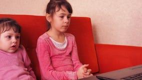 Kinderen die in laptop spelen Twee meisjes zijn gedrukt op laptop Twee zusters die op de sinaasappel zitten gaan liggen het bekij stock videobeelden