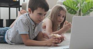 Kinderen die media op inhoud op laptop letten stock videobeelden