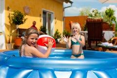 Kinderen die met bal in waterpool spelen Stock Fotografie