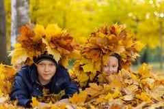 Kinderen die met bladeren in het park spelen royalty-vrije stock afbeelding