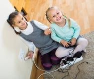 Kinderen die met contactdozen en elektriciteit binnen spelen stock afbeelding