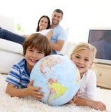Kinderen die met een aardse bol spelen stock fotografie