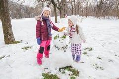 Kinderen die met een Sneeuwman in het Park bij de Winterdag spelen stock afbeelding