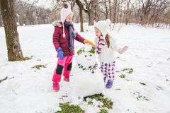 Kinderen die met een Sneeuwman in het Park bij de Winterdag spelen stock afbeeldingen