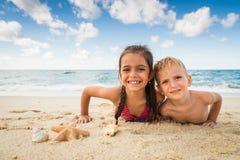 Kinderen die met een zeester op het strand spelen stock fotografie